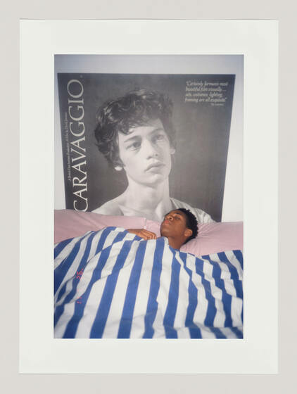 A large magazine cover poster on a wall, in front, a Black man sleeping in a bed with striped covers and pink pillows.