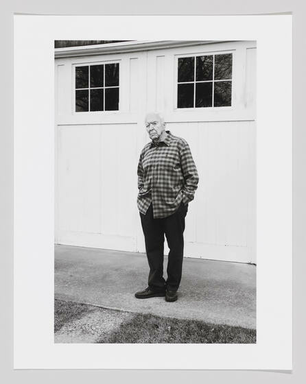 A black and white photo of Jasper Johns in a flannel standing with hands in his pockets.