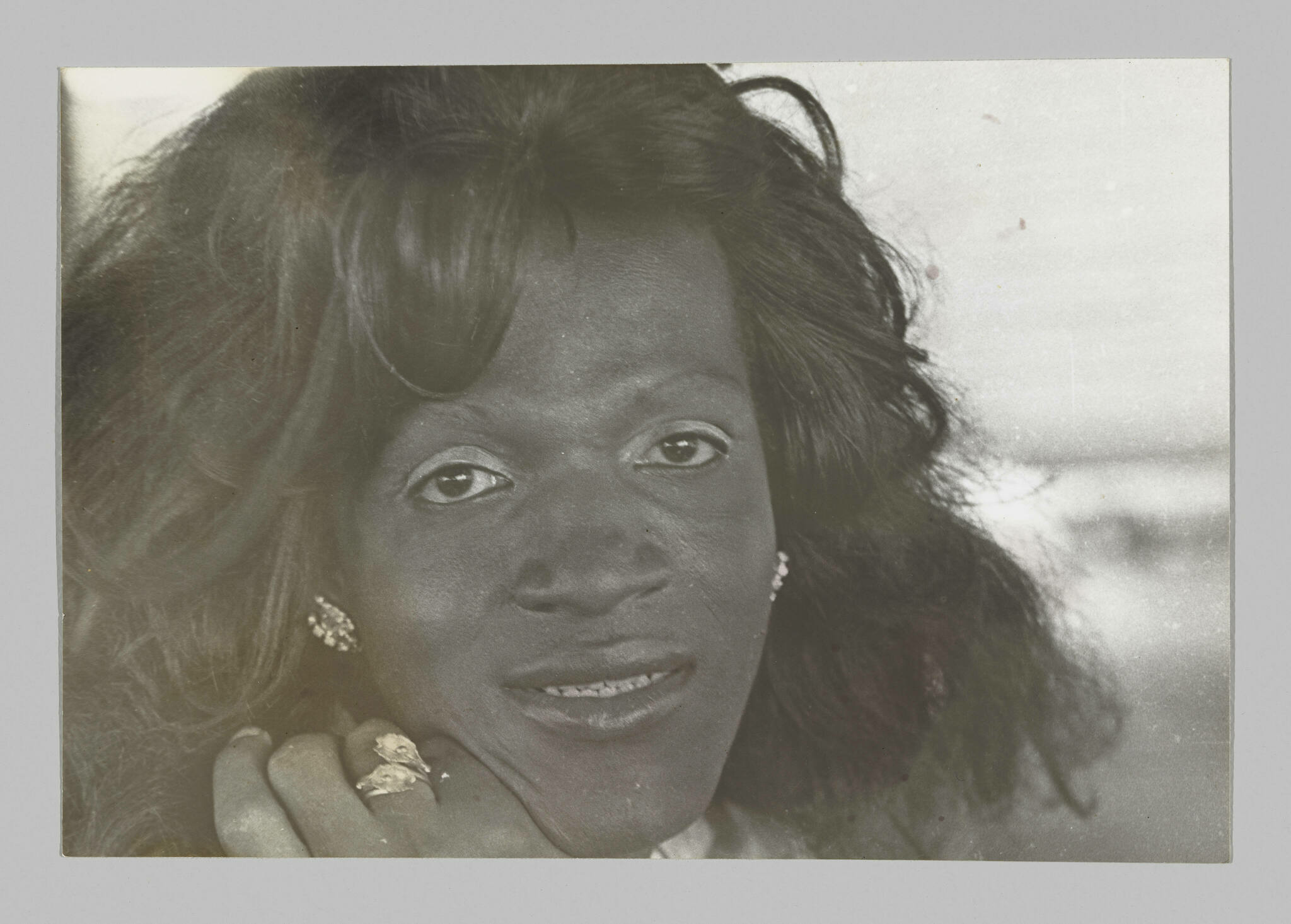 Closely cropped portrait of a Black trans person gazing into the camera, with shoulder-length hair and glittering jewelry