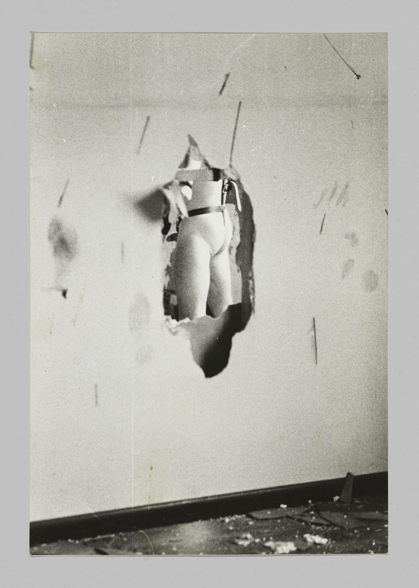 A hole in a dilapidated wall reveals a nude man's lower back, upper legs, and semi-erect penis from a three-quarter rear view.
