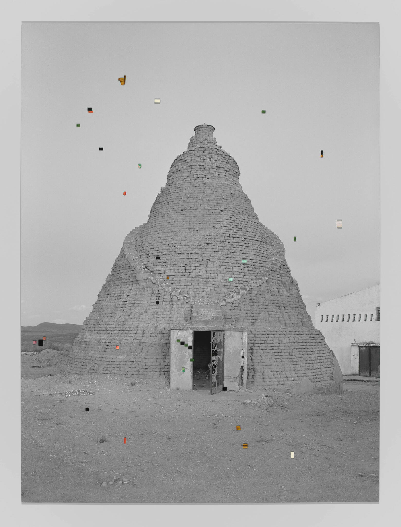 A black-and-white photograph of a large, conical grain silo is adorned by small, colorful precious gems