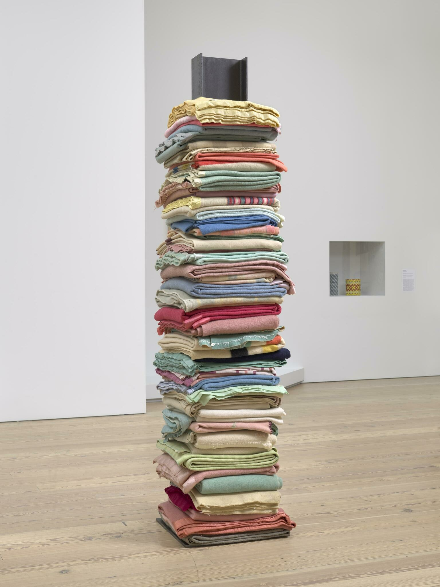 Brightly-colored reclaimed wool blankets stacked in an upward pile and punctured in the center by a vertical steel I-beam