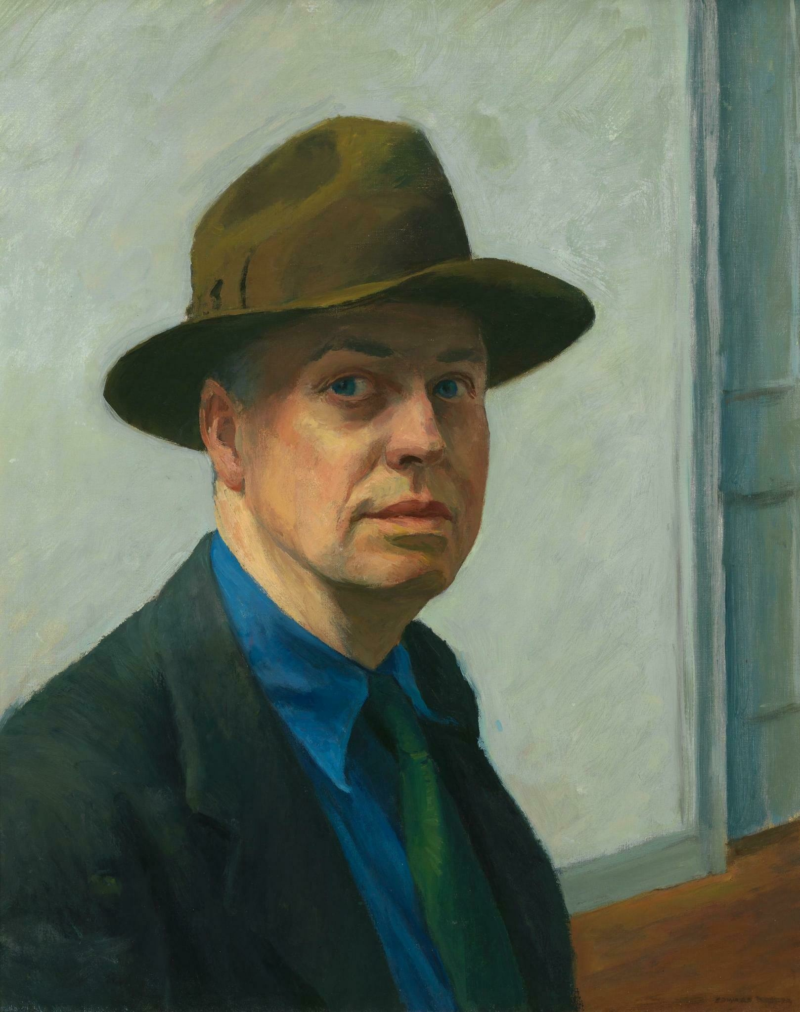 A white man stares at us in a fedora, jacket, tie, and bright blue shirt that matches the color of his eyes
