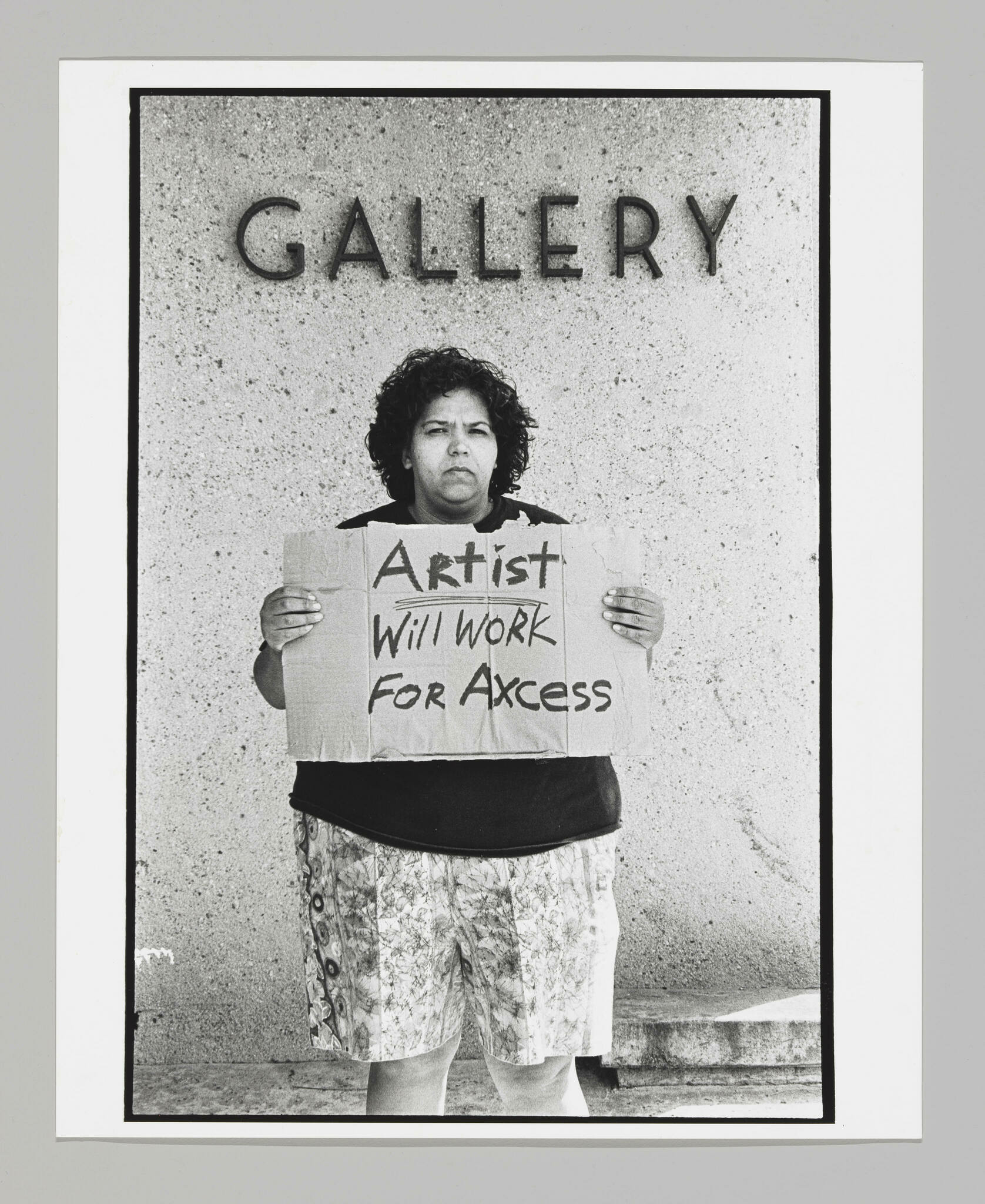 """Standing in front of sign that says """"Gallery,"""" a large Latinx woman holds a cardboard sign that reads """"Artist Will Work for Acess."""" The last word is mispelled."""