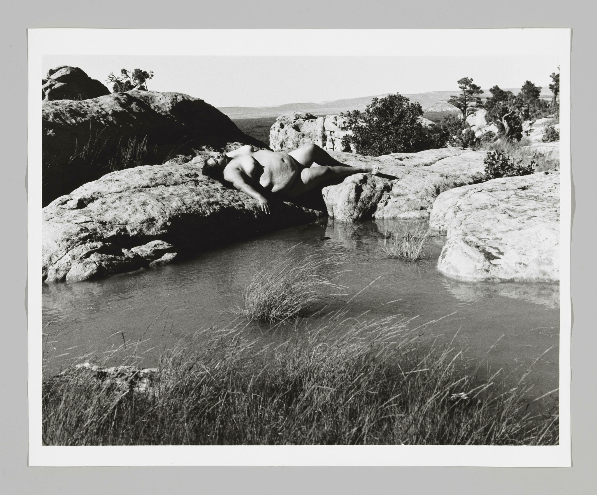 A large, naked woman reclines serenely at water's edge in a rocky landscape