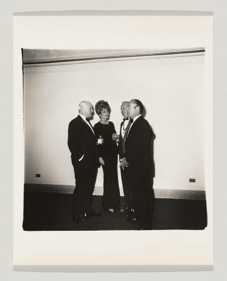 A group of three men and a woman wear black tie attire and stand in a circle