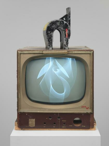 A 1960s television set with a horseshoe magnet on top, the image on screen warped into wispy, overlapping curves