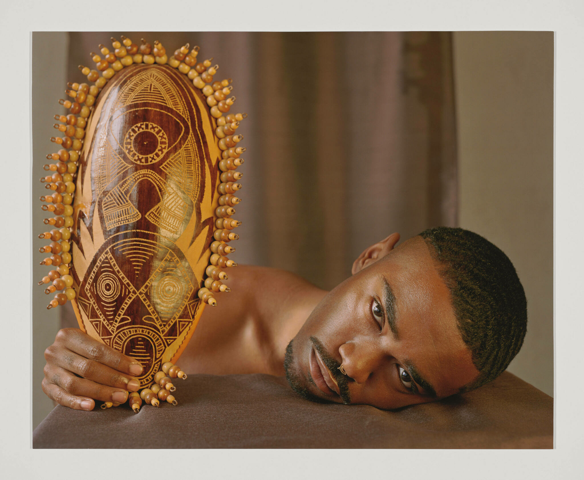 A Black man lies his head on a brown cloth in the foreground, holding an etched and beaded African mask