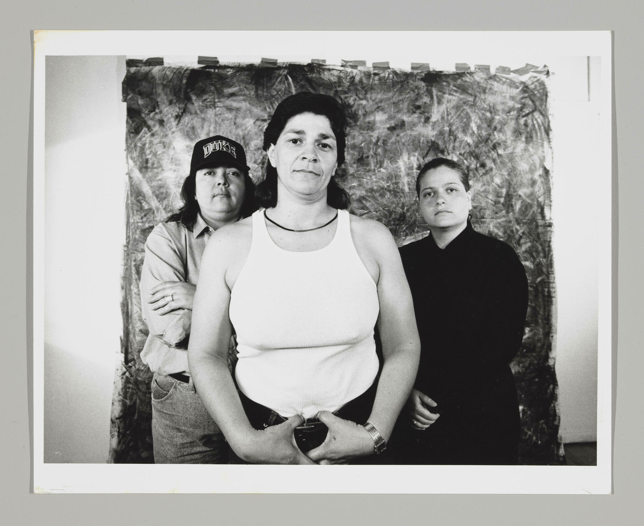 Three figures stand in front of a studio photography backdrop