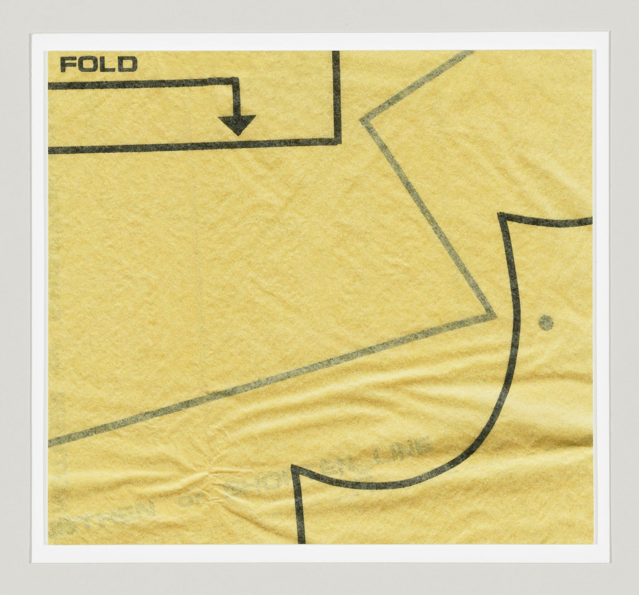 Detail of yellow tissue sewing pattern with printed curves, lines, and text reading FOLD with a directional arrow.