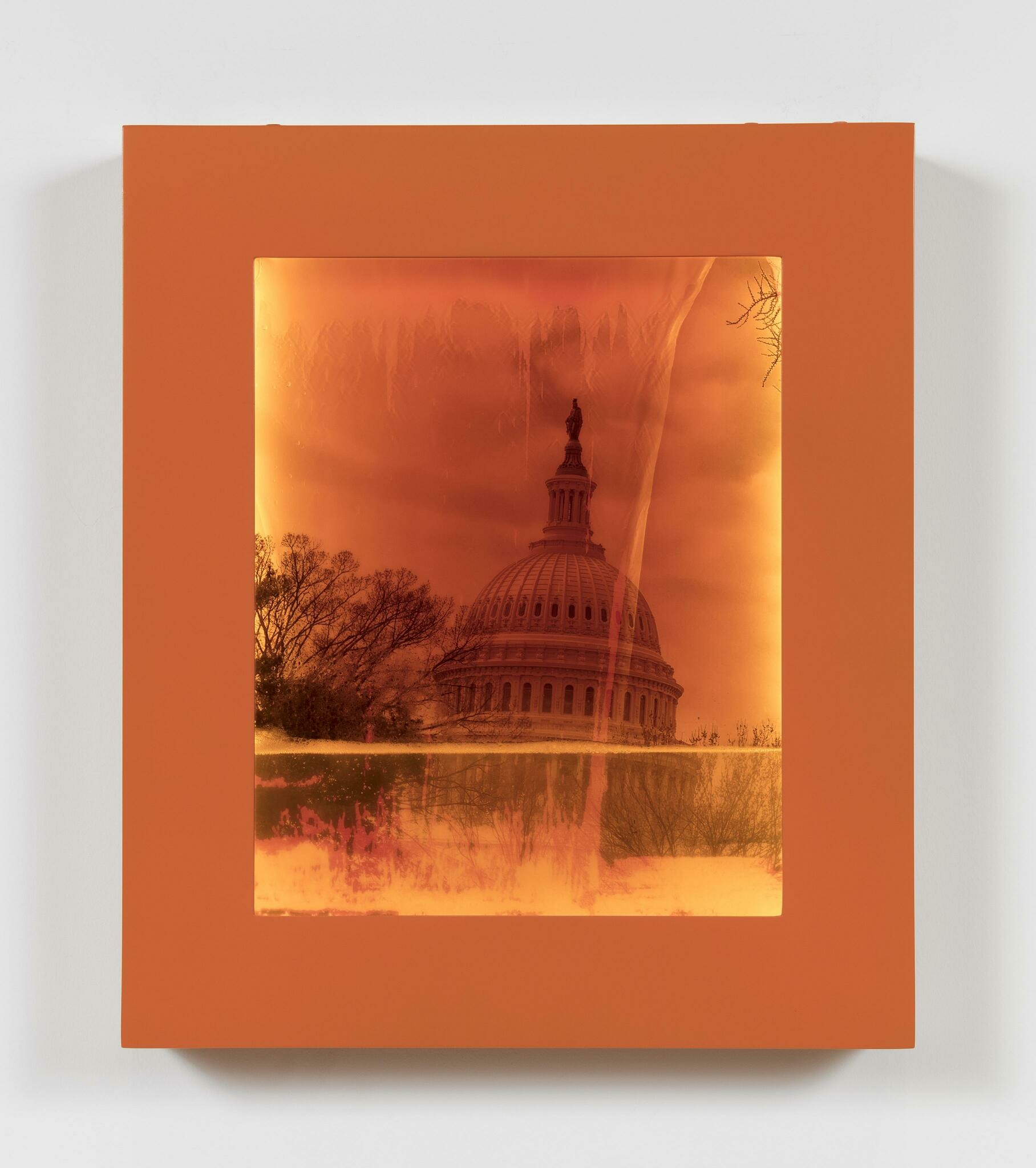 Photo of the United States Capitol building contained within an orange frame filling with water