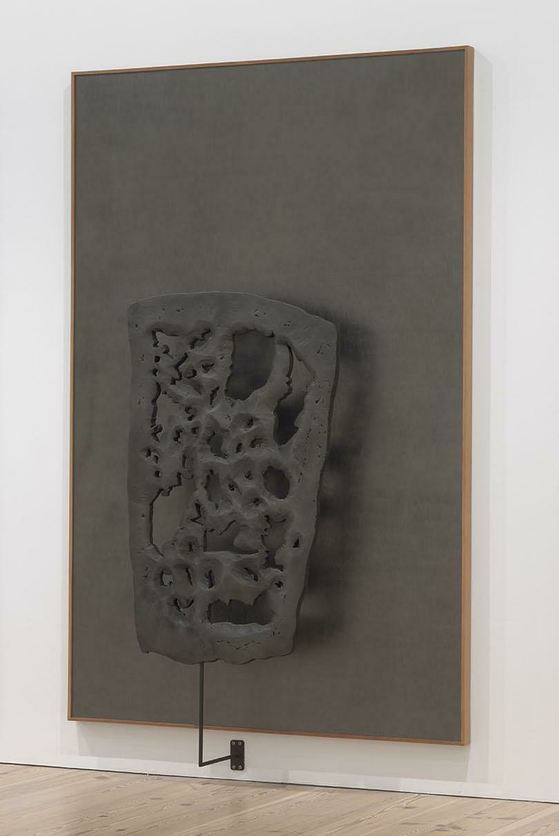 A perforated and craggy three-dimensional sculpture seems to hover in front of a sharply rectangular dark gray canvas.