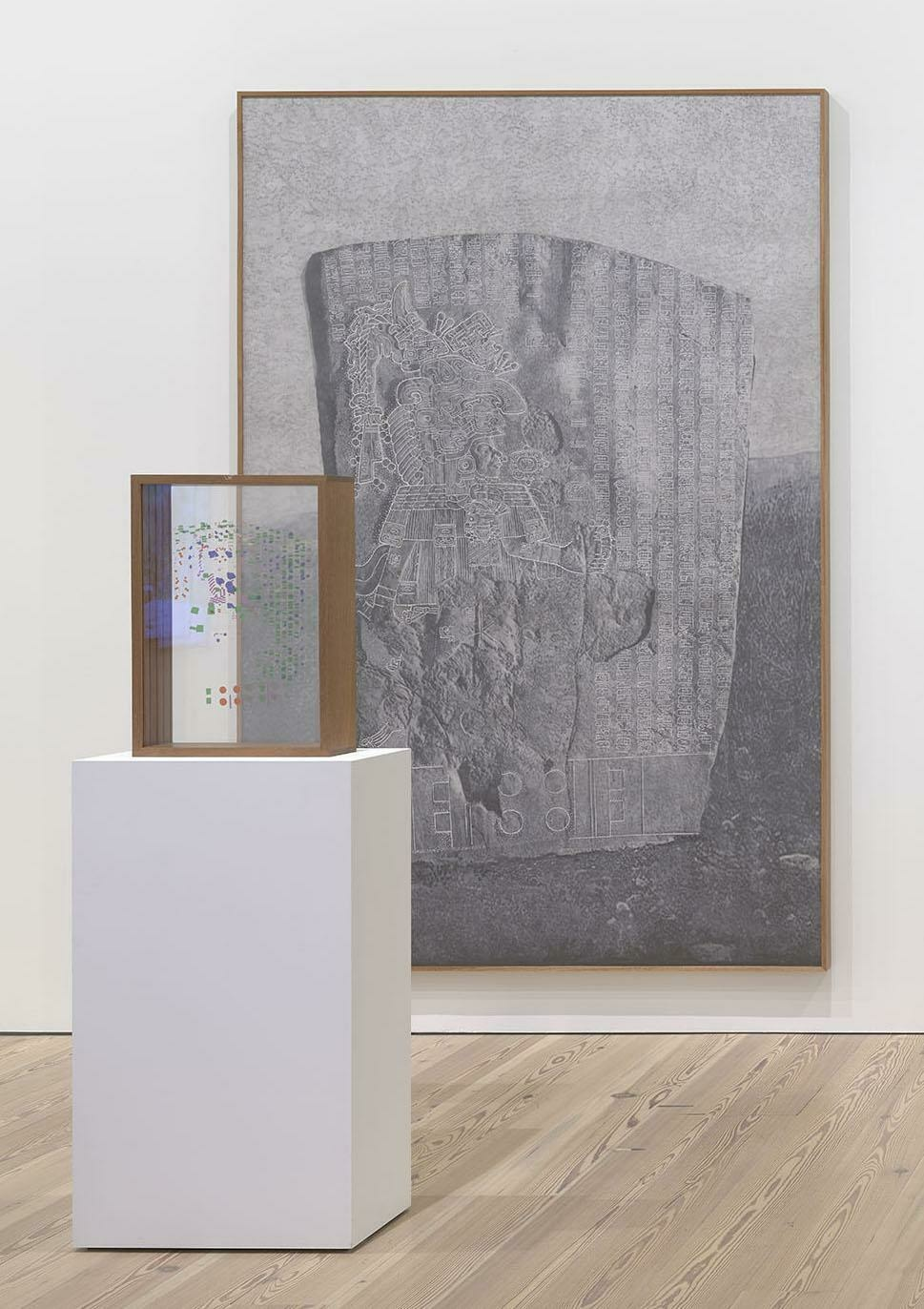 A meticulous graphite drawing of La Mojarra Stela sits behind a wooden box of plexiglass slides with colorful characters