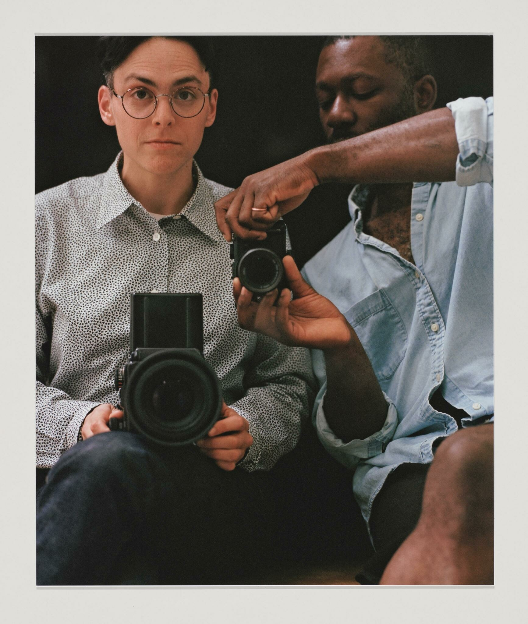 Two seated people, a white person in glasses and a Black person with a mustache, photograph their reflections with different size cameras