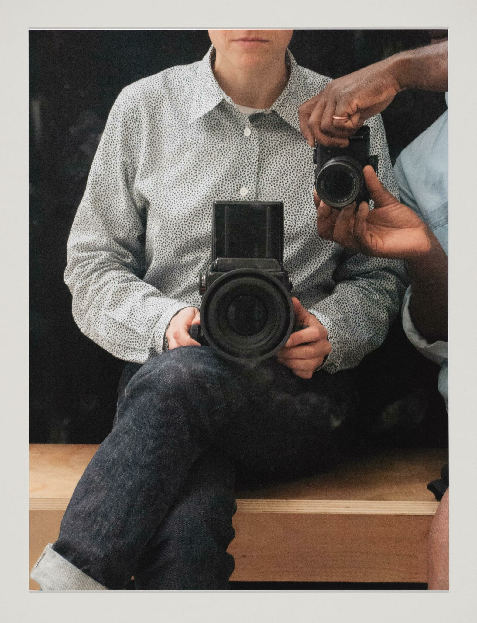 A seated white person holds a large camera in their lap, their face cropped, and a Black person reaches into the frame holding a smaller camera