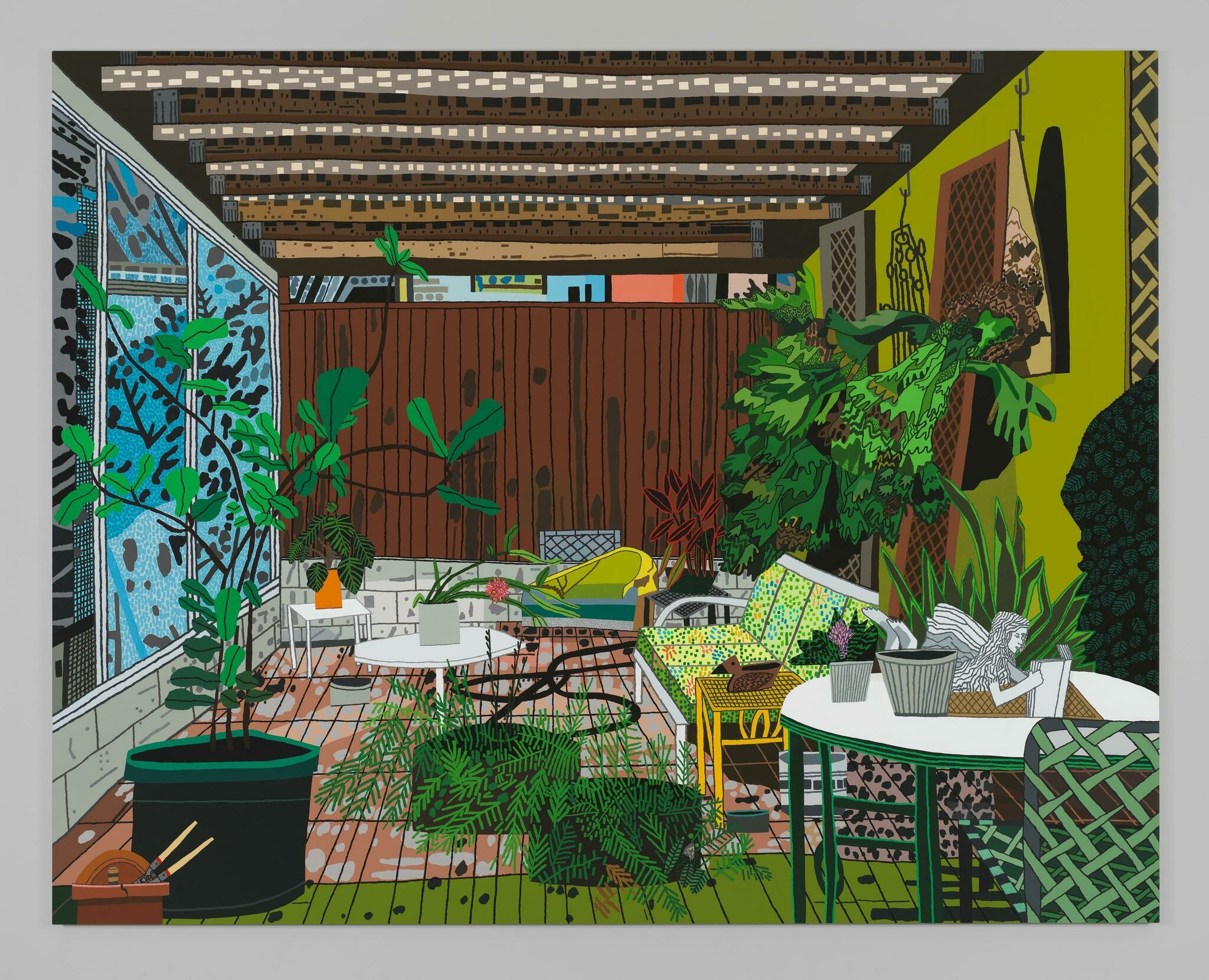 A cluttered, leisurely room with low seating and an array of potted plants