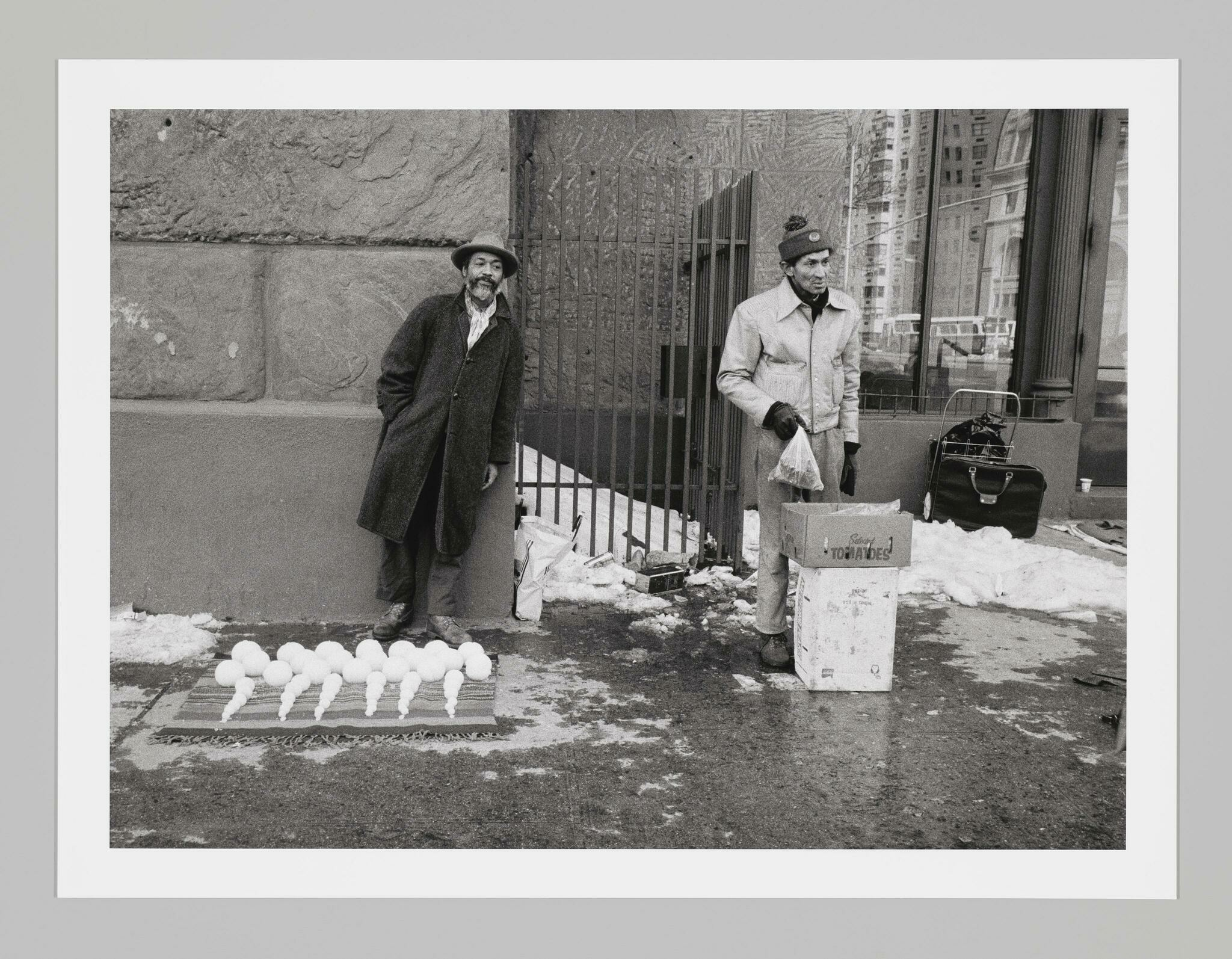 Two men stand on a snowy sidewalk selling items. The man on the left, artist David Hammons, sells differently sized snowballs.