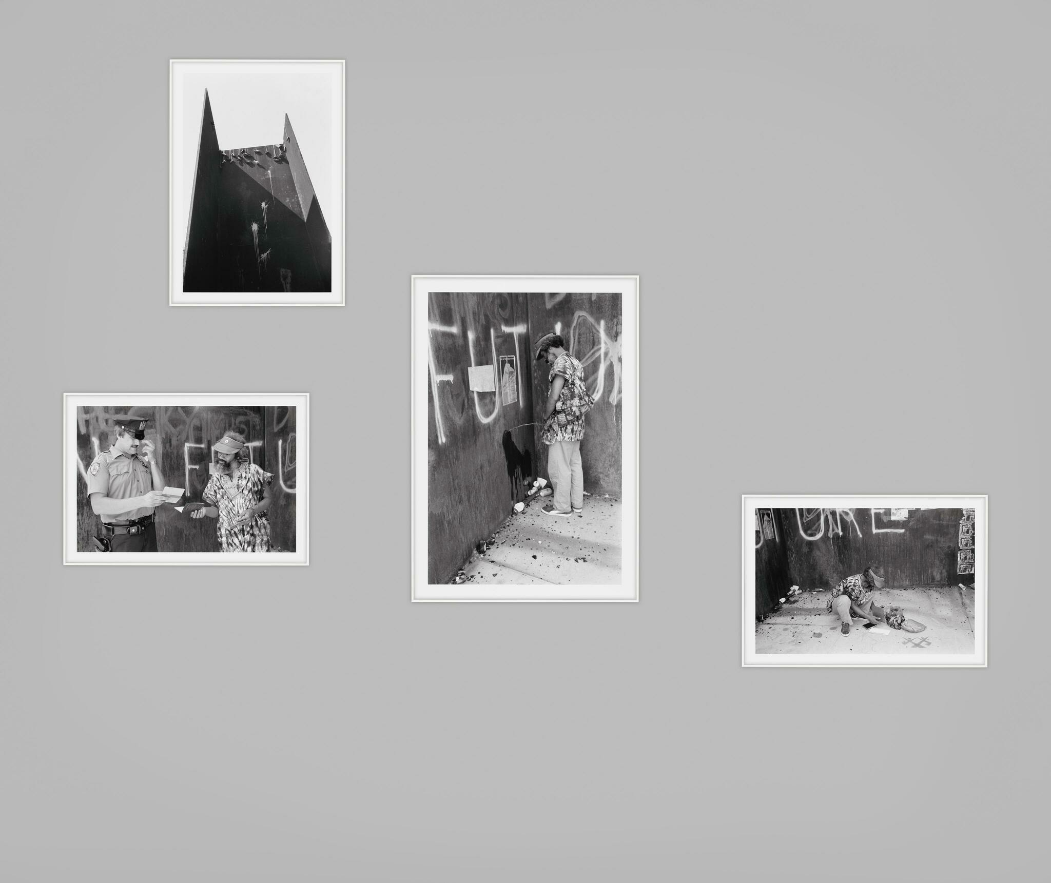 Photographs of steel sculpture. One with shoes dangling and three showing a Black man: urinating, crouching and with white police officer.