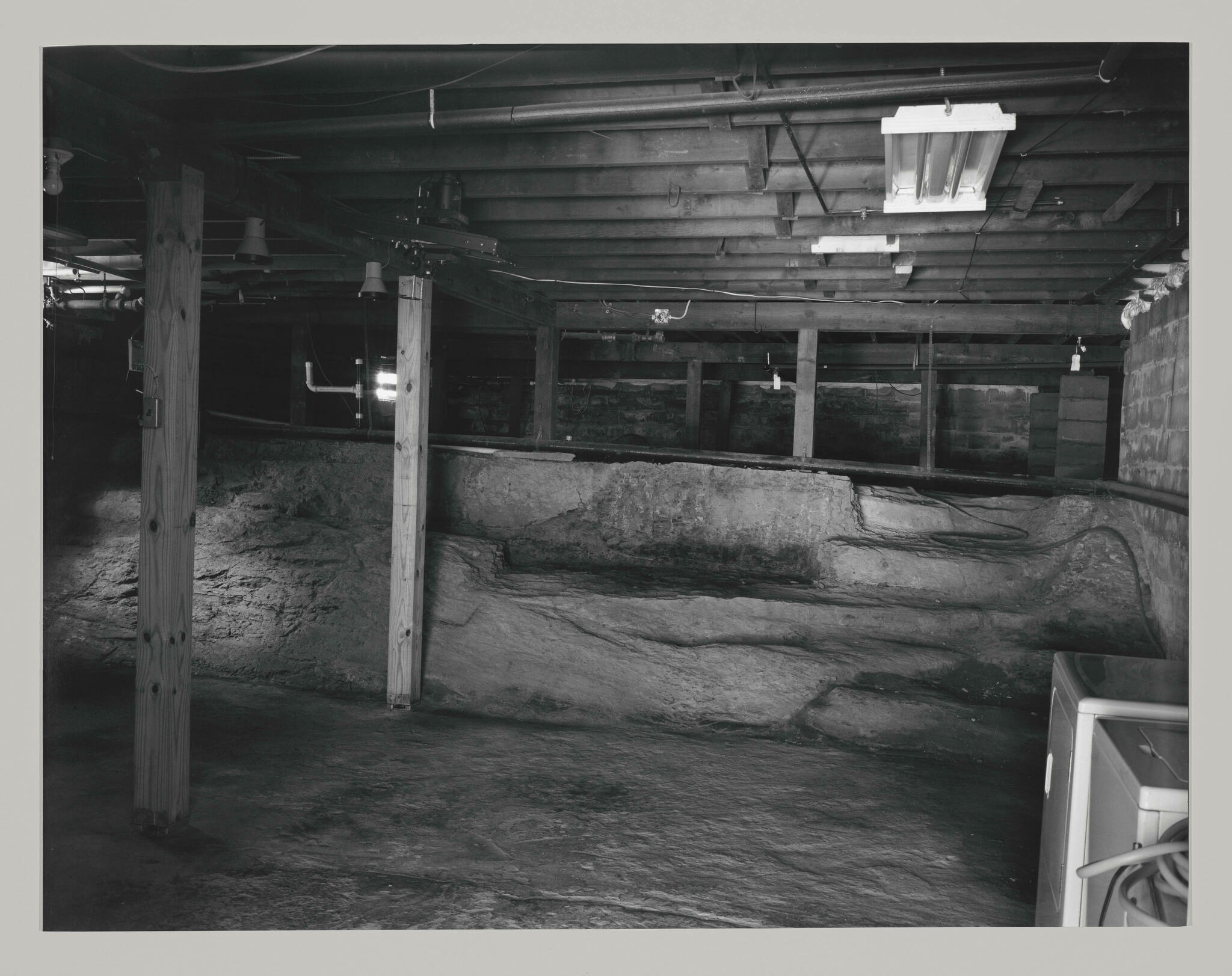 A dark empty room with a low ceiling of exposed, wooden beams and an uneven dirt floor full or slopes. A washer and dryer sit in the corner of the frame.