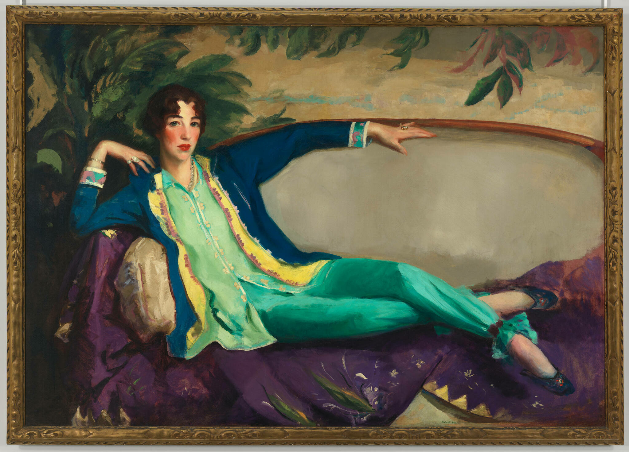 A white woman with short brown hair, rosy cheeks, and dressed in a flowy teal and blue shirt and pants lounges on a sofa while gazing intently.