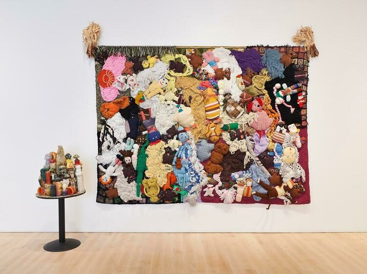 A horizontal canvas covered in stuffed animals and afghan blankets in muted colors.
