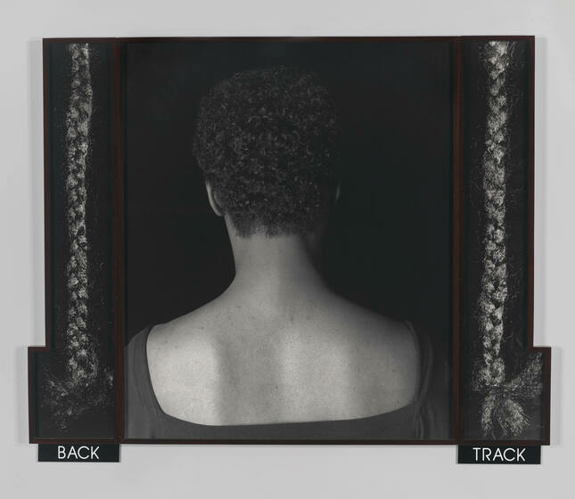 """The head and shoulders of a short-haired Black woman in a dark blouse with her back to the camera. Single strands of dark braided hair hang on either side of her above text that reads """"BACK"""" and """"TRACK"""""""