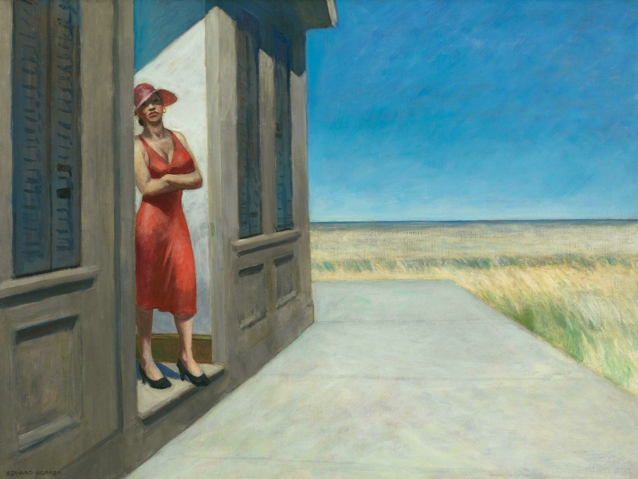 A white woman wearing a a burnt orange dress and sun hat crosses their arms and leans aganist a doorway