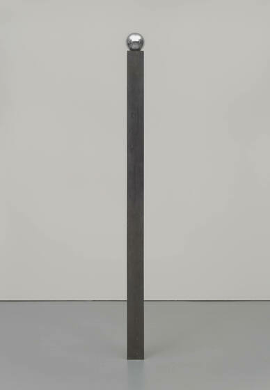 A thin, dark bronze column standing alone with a balanced steel ball resting on top of the exact diameter