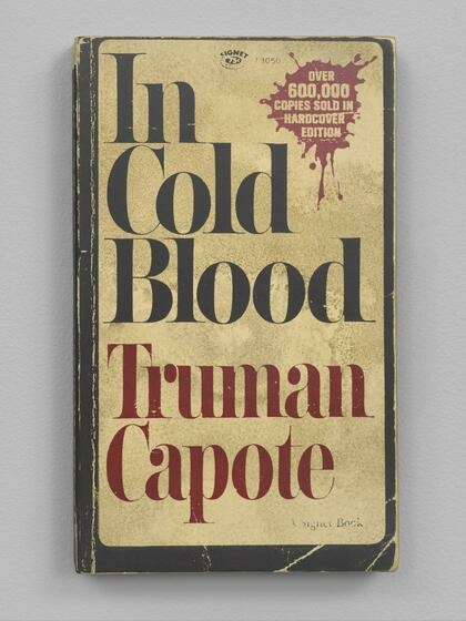 """The front cover of a book titled """"In Cold Blood"""" with worn edges and frayed corners"""