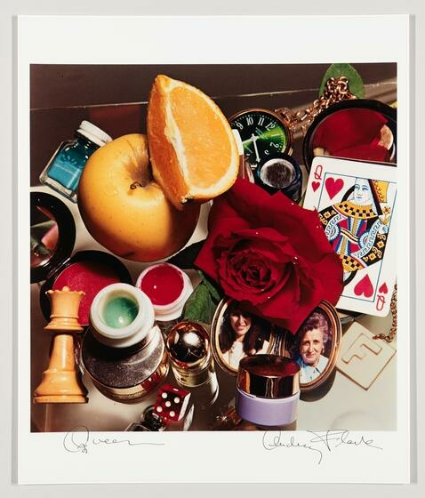 A motley pile of objects, including a red rose, a locket, a chess piece, a sliced orange, and a Queen playing card.