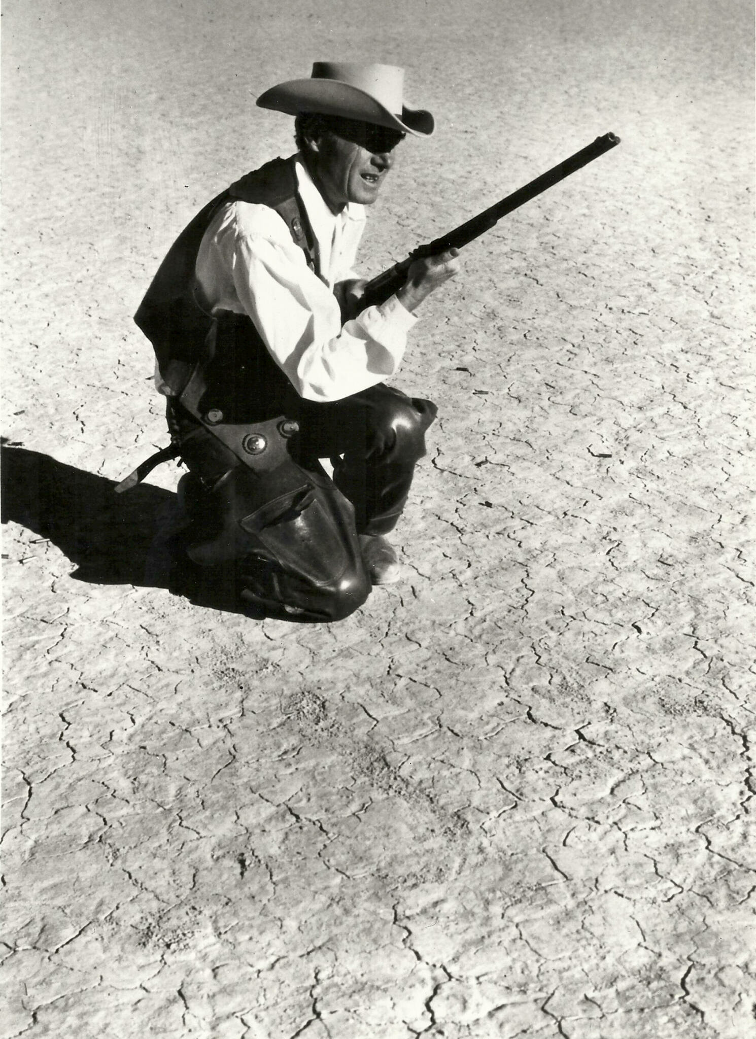 Black and white film still of a man in Western attire kneeling with a rifle on a cracked desert terrain