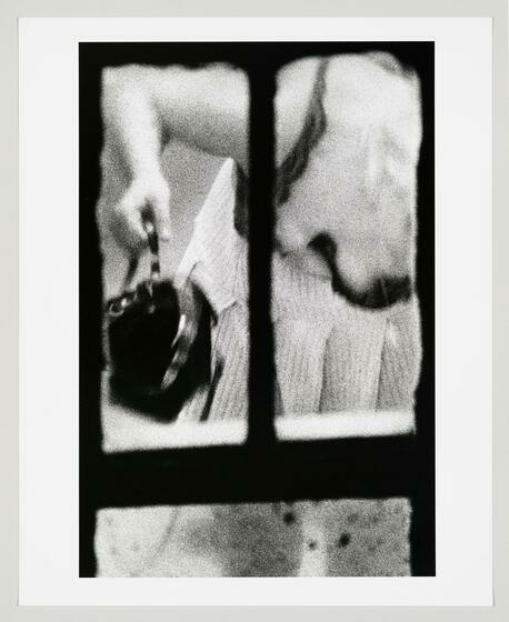 A grainy image seen from a window, shows the arm and chest of a woman as she bends to grad her handbag