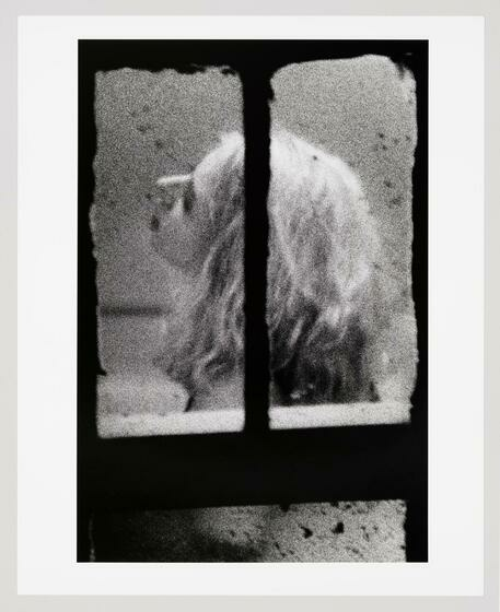 A grainy image seen from a window of a blonde white woman as she fixates her gaze upwards