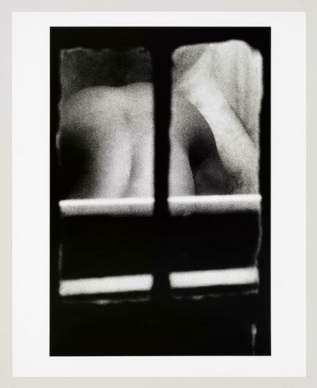 A grainy image seen from a window shows a woman's nude backside as she arches her back