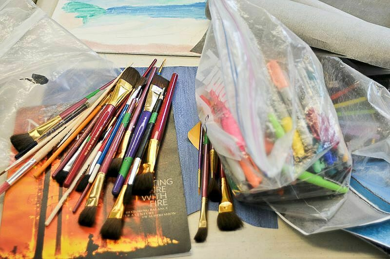paint brushes on top of artwork