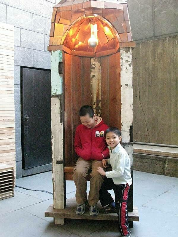 Two children laughing in the sculpture exhibit