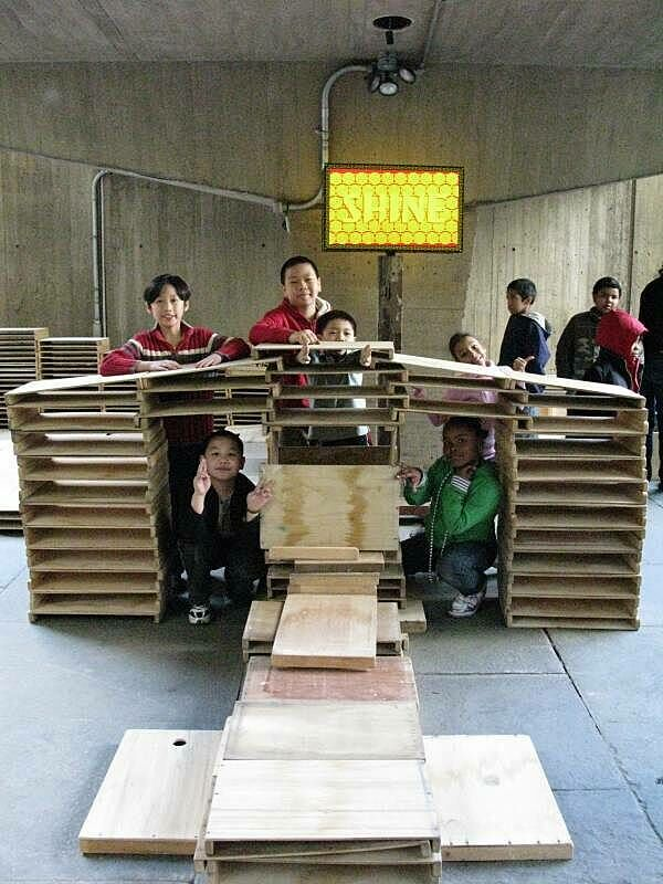Kids exploring the wood sculpture they built