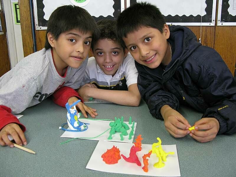 Three children posting with the sculpture models they made