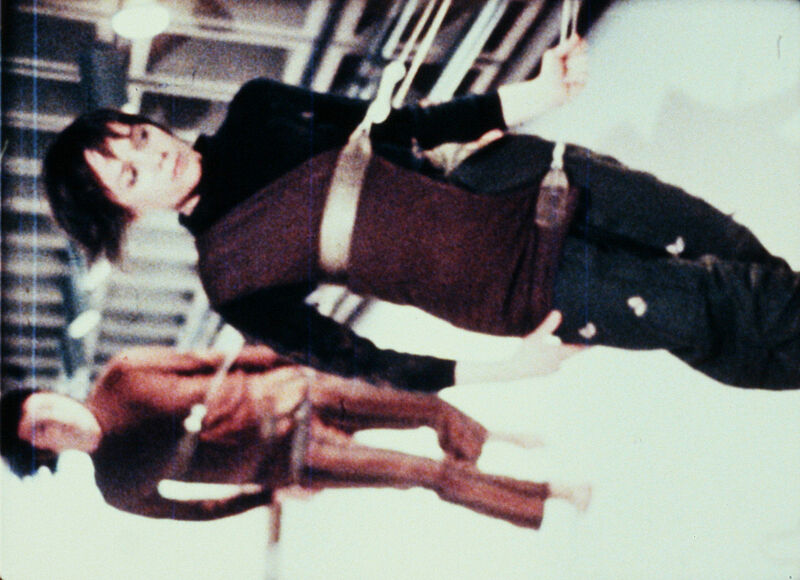 A film still of two people attached to a wall by harnesses.