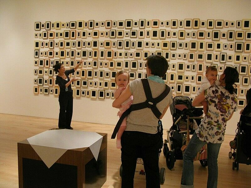 A baby stares at the camera as parents take in Allan McCollum's 288 Plaster Surrogates.