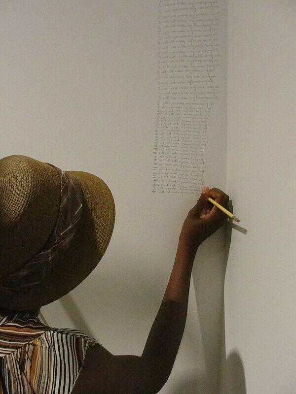 A woman writes on a wall.