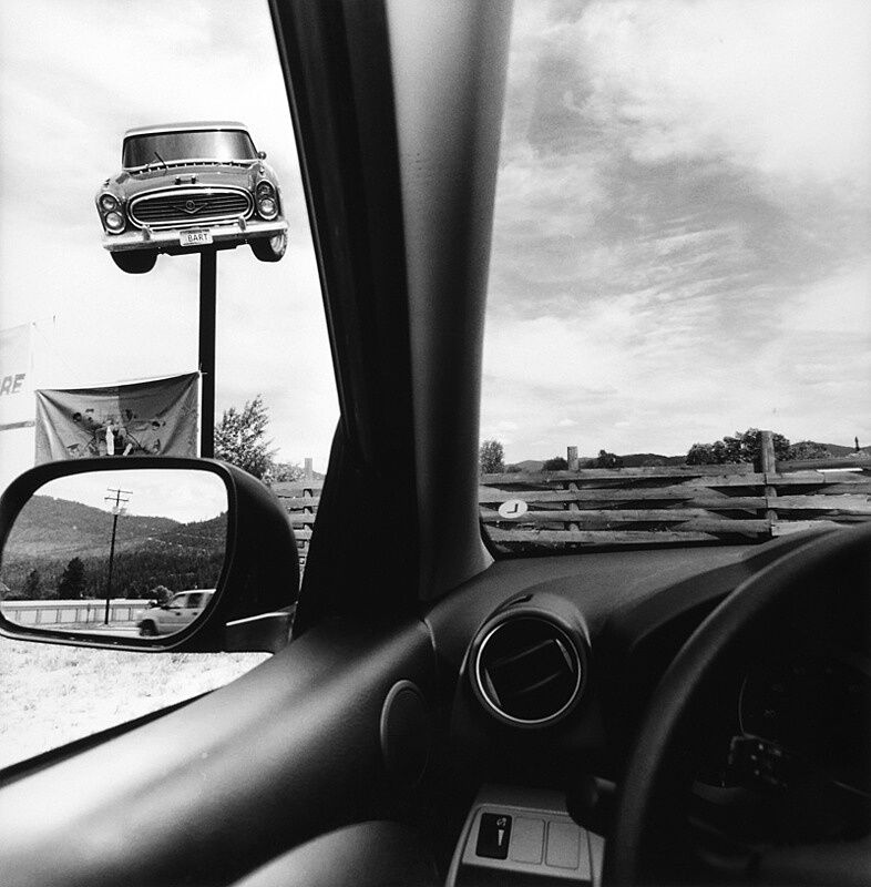The view from the driver's seat in a car looking at another car on a pole.