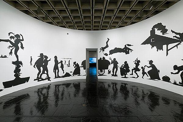 Cut paper silhouettes of people by Kara Walker cover a gallery wall.