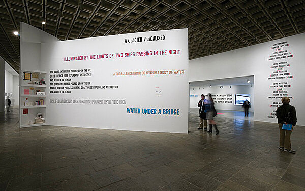 A gallery installation featuring text art by Lawrence Weiner.