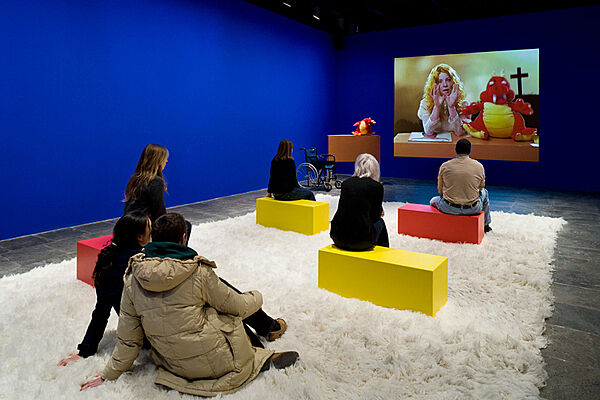 People watching a video in a gallery with a furry rug.
