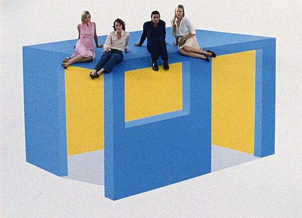 Three women and a man sit on a blue and yellow box.