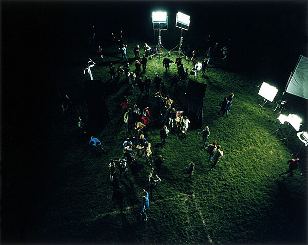 A crowd assembles on green grass under flood lights.