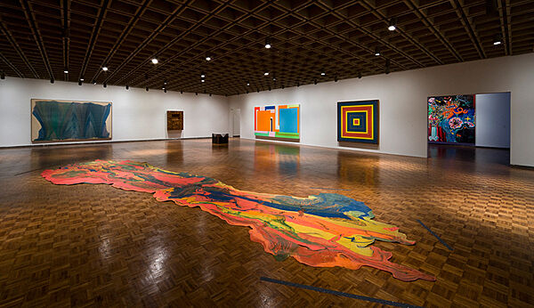 Colorful abstract paintings line walls and floor.