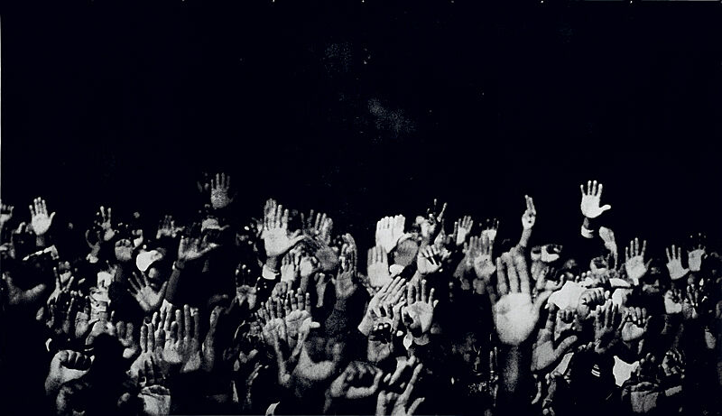 A silkscreen print of hands raised in the air against a black background.