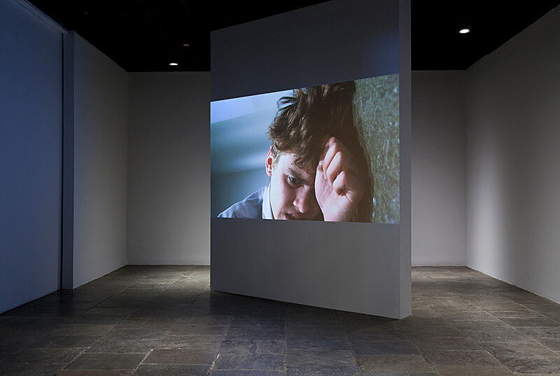 A video still of a man holding his hand to his head in a gallery installation.